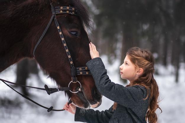 Mädchen und braunes pferd im winter