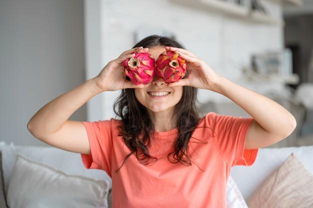 Mädchen und drachenfrucht. freudiges mädchen, das tropische früchte genießt.