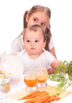 Mädchen und ein kleiner junge, bruder und schwester und karottensaft isoliert auf weißem hintergrund