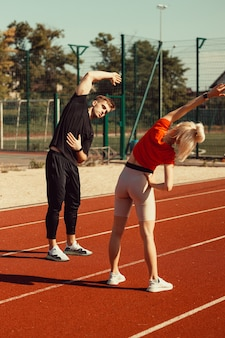 Mädchen und ein mann machen ein aufwärmen vor sportübungen im schulstadion