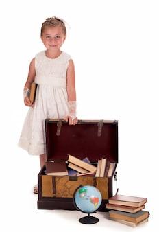 Mädchen und eine truhe mit büchern. kleines mädchen, das mit überraschung auf weißem hintergrund in einen kofferraum schaut