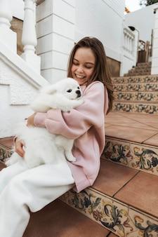 Mädchen und flauschiger hund auf der treppe