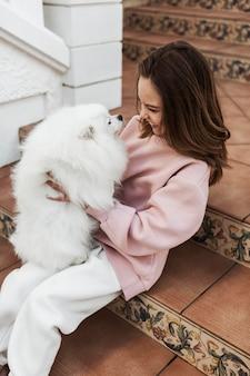 Mädchen und flauschiger hund auf der treppenseitenansicht