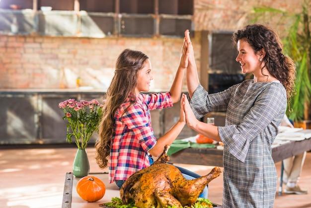 Mädchen- und frauenhändchenhalten nähern sich gebackenem huhn