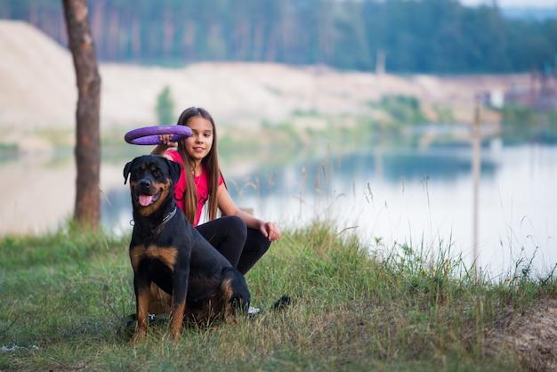 Mädchen und hund am rand einer klippe spielen mit einem ringel und genießen den morgen im wald