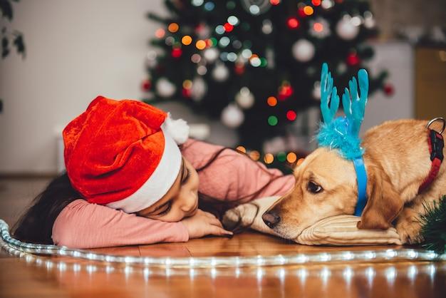 Mädchen und hund, die durch den weihnachtsbaum niederlegen