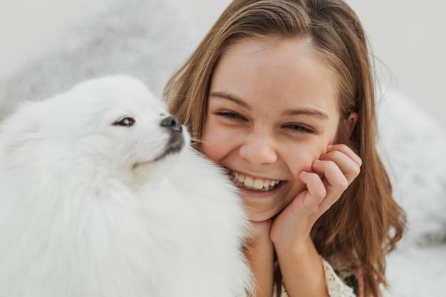 Mädchen und hund sind glücklich und spielen