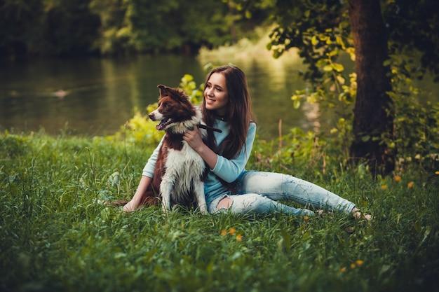 Mädchen und hund sitzen auf dem rasen