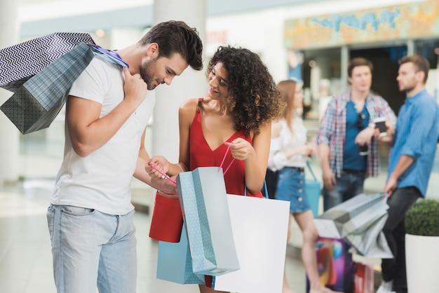 Mädchen und ihr freund kaufen im einkaufszentrum ein.