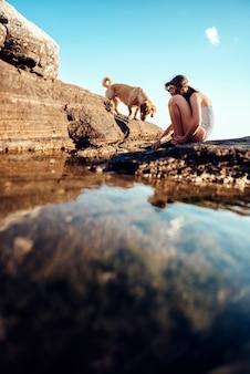 Mädchen und ihr hund, die felsigen strand erforschen