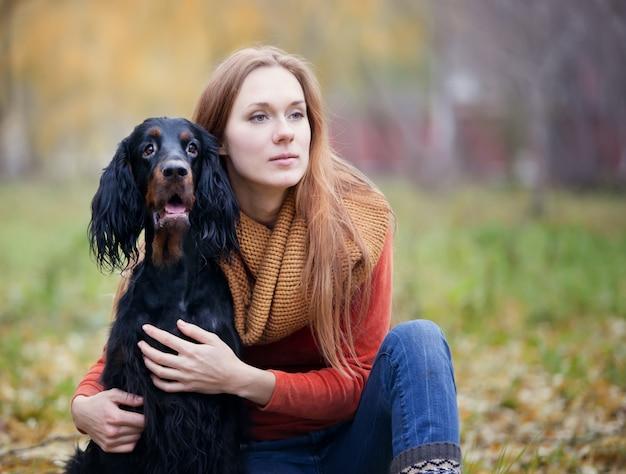 Mädchen und ihr hund gordon setter im herbst park