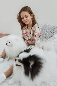 Mädchen und ihre hunde auf dem bett