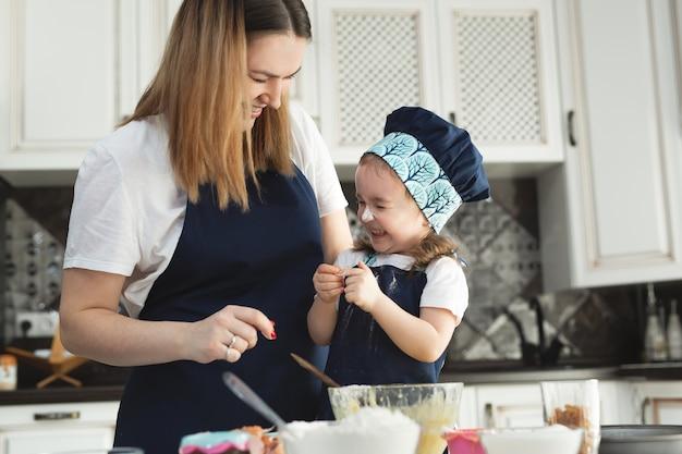 Mädchen und ihre mutter in passenden schürzen und mützen spielen, während teig in der küche knetet