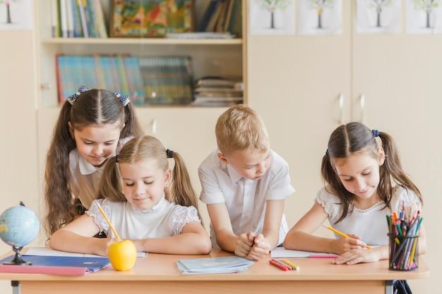 Mädchen und junge, die das studieren der freunde betrachten