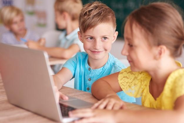 Mädchen und junge, die den computer im klassenzimmer benutzen Kostenlose Fotos