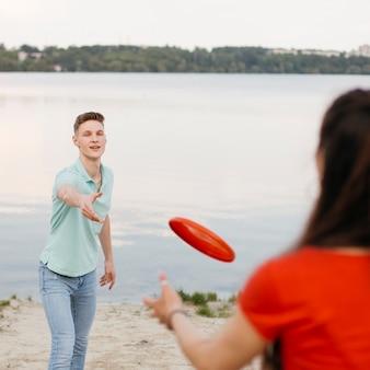 Mädchen und junge, die mit rotem frisbee spielen
