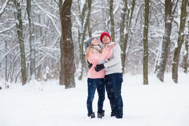 Mädchen und junge, die schneeflocken im winterwald fangen