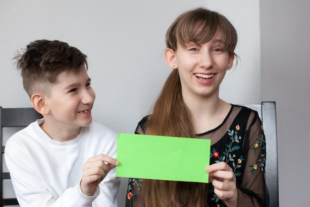 Mädchen und junge halten blatt grünes papier für ihren text. lächelnde schwester und bruder zeigen leere grüne karte für einfachen text