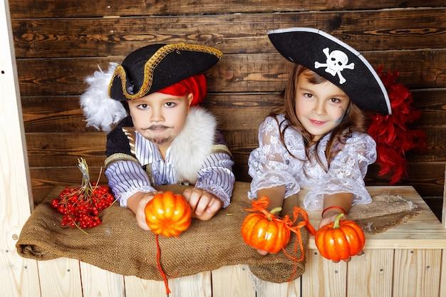 Mädchen und junge in piratenkostümen mit halloween-dekorationen