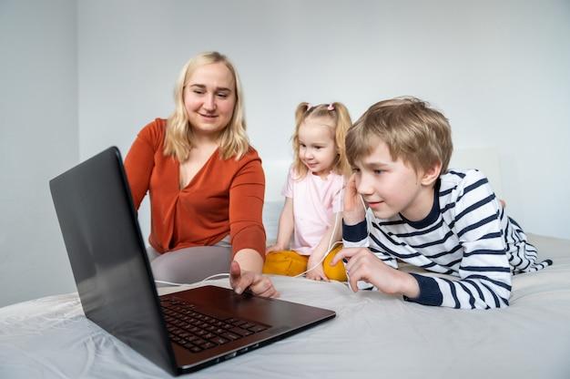 Mädchen und junge mit laptop und kopfhörer zu hause mit mutter