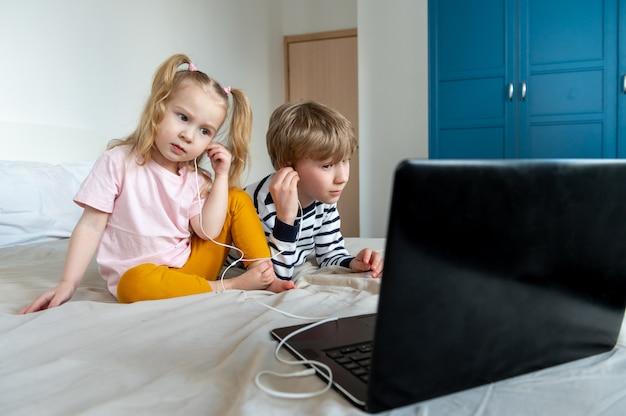 Mädchen und junge mit laptop und kopfhörer zu hause