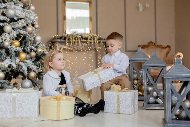 Mädchen und junge öffnen weihnachtsgeschenke