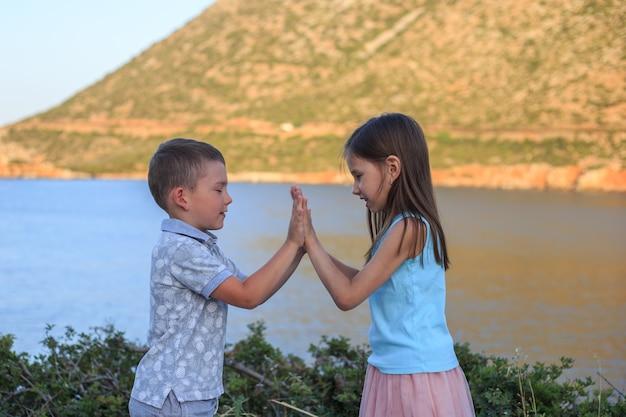 Mädchen und junge zusammen im freien. kleiner bruder spielt mit älterer schwester.