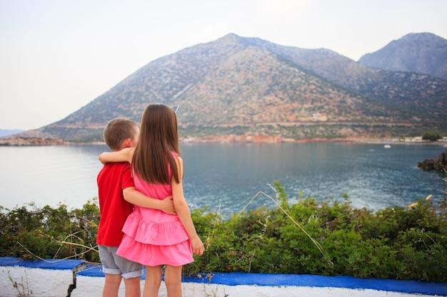 Mädchen und junge zusammen im freien. kleiner bruder umarmt ältere schwester in der nähe des meeres.