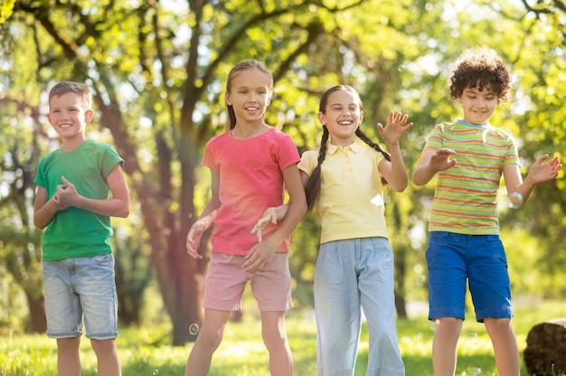 Mädchen und jungen, die seifenblasen fangen