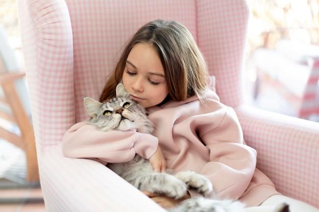 Mädchen und katze sitzen in einem sessel