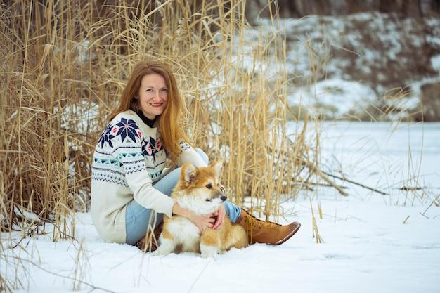 Mädchen und kleiner süßer corgi flauschiger welpe im freien. winter