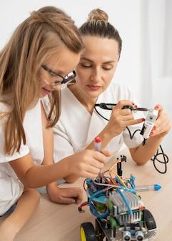 Mädchen und lehrerin, die wissenschaftsexperimente mit roboterauto tun