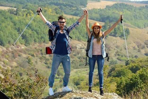 Mädchen und mann bestiegen den berg und hoben die hände.