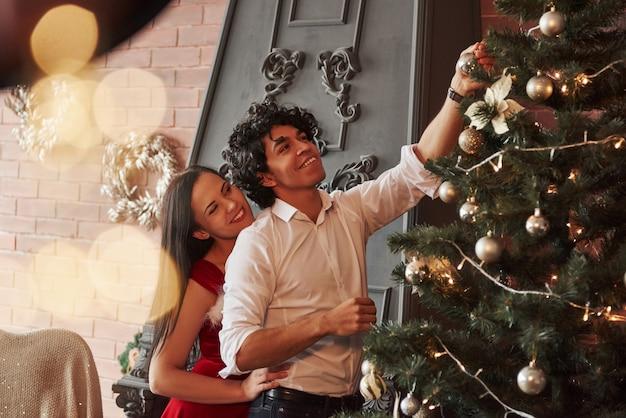 Mädchen und mann lächelt während des prozesses. romantische paare, die oben weihnachtsbaum im raum mit brauner wand und kamin ankleiden