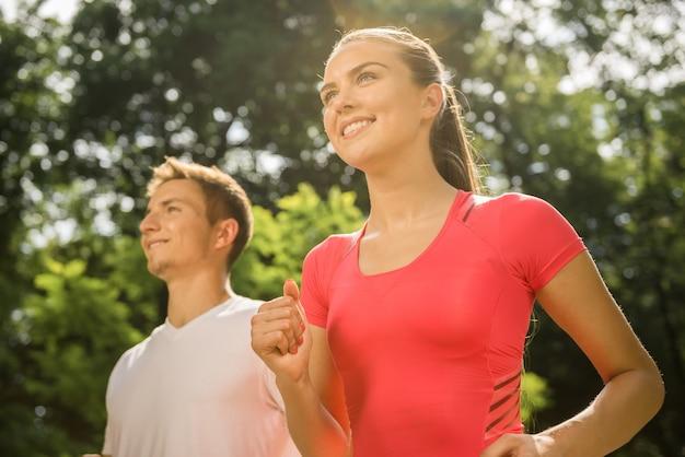 Mädchen und mann treiben in den frühen morgenstunden sport.