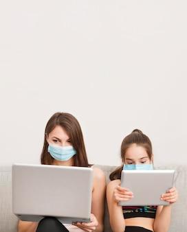 Mädchen und mutter auf der couch mit elektronischem gerät