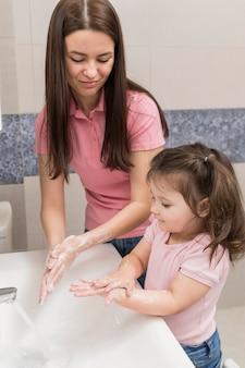 Mädchen und mutter hände waschen