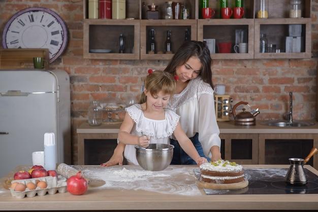 Mädchen und mutter kochen einen kuchen