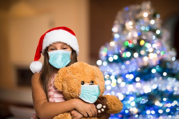 Mädchen und teddybär tragen eine maske, weihnachtskoronavirus und pandemiekonzept