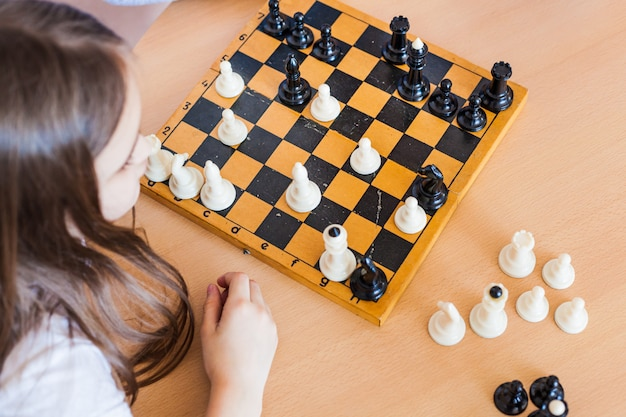 Mädchen und vater spielen ein spiel zu hause, schach, rätsel für die entwicklung des gehirns, mentale intelligenz