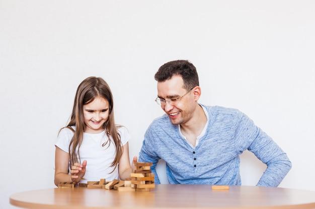 Mädchen und vater spielen zu hause ein spiel, kosten einen turm aus blöcken, würfeln, jenga, rätsel für die entwicklung des gehirns, mentale intelligenz
