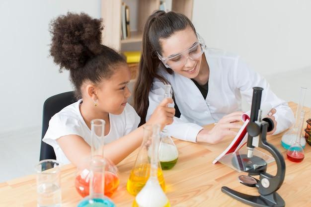 Mädchen und wissenschaftlerin, die spaß beim lernen der wissenschaft haben