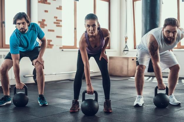 Mädchen und zwei kerle, die gewichte im fitness-club anheben.