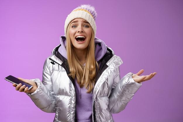 Mädchen verärgert schreien, erklären fehlende chance lebenszeit fühlen bedauern sprechen leidenschaftlich gespreizte hände seitwärts halten smartphone aussehen gestört enttäuscht, stehend lila hintergrund.