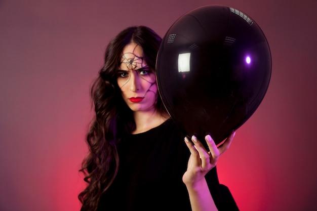 Mädchen verkleidet als hexe mit ballon in der hand