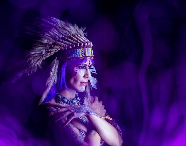 Mädchen verkleidet als indianer mit federn auf dem kopf posiert im dunkeln für lightpainting-fotografie.