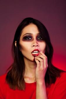 Mädchen verkleidet als vampir ihren mund berühren