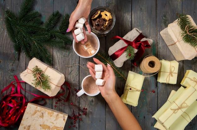 Mädchen versiegeln geschenke und trinken kakao mit marshmallows