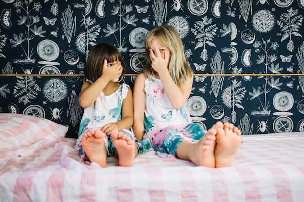 Mädchen verstecken gesichter hinter den händen