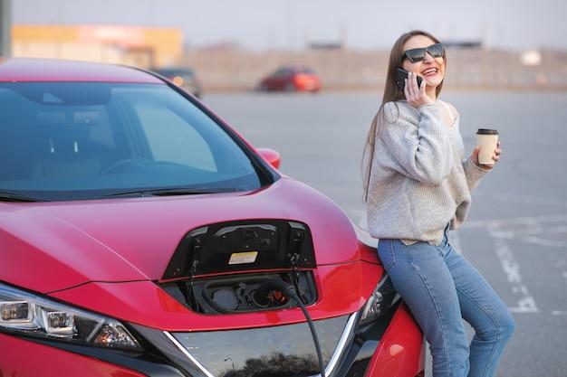 Mädchen verwenden kaffeegetränk, während sie smartphone benutzen und netzteil warten verbinden sie sich mit elektrofahrzeugen, um die batterie im auto aufzuladen